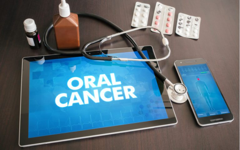 tablet that displays oral cancer with pills around it